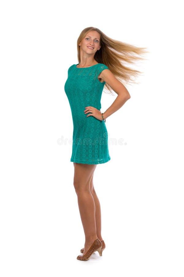 Красивая девушка в платье бирюзы с превращаясь волосами в стоковое изображение rf
