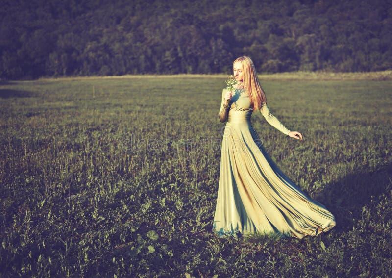 Красивая девушка в платье длинного зеленого цвета с букетом цветков в onnature лета стоковое фото rf