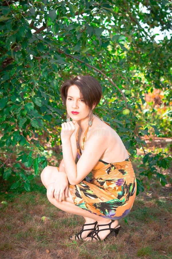 Красивая девушка в платье сидя в саде стоковое фото rf