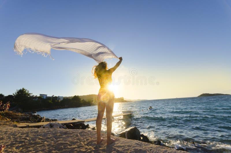 Красивая девушка в пляже держа покрашенную часть ткани стоковые изображения rf