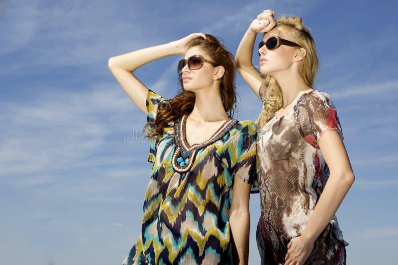 Красивая девушка 2 в солнечных очках на небе предпосылки голубом стоковое фото rf