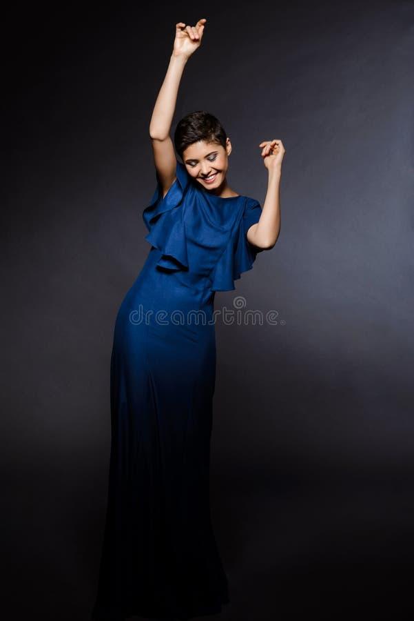 Красивая девушка в танцах платья вечера, усмехаясь над серой предпосылкой стоковые фотографии rf