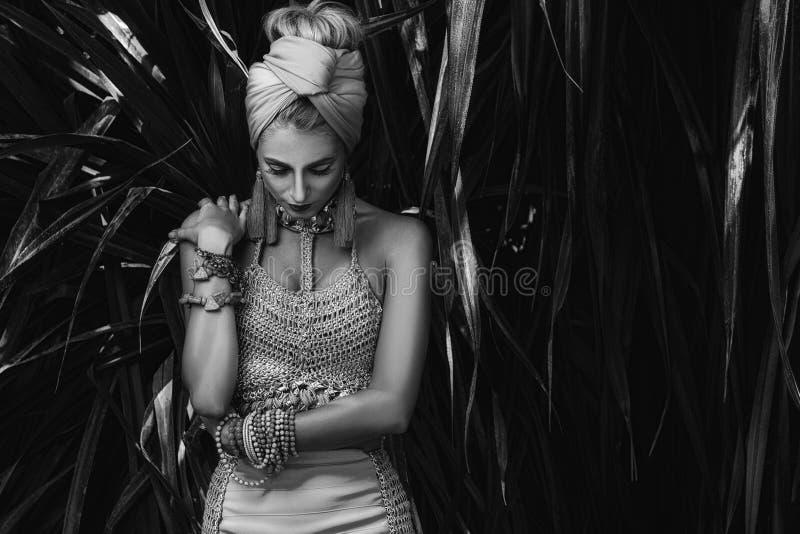 Красивая девушка в тюрбане представляя в саде стоковые фото