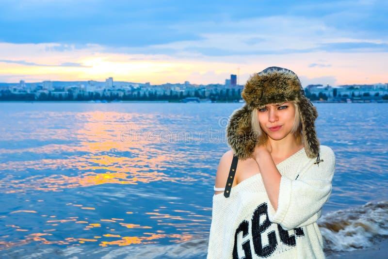 Красивая девушка в шляпе представляя на заходе солнца стоковое изображение