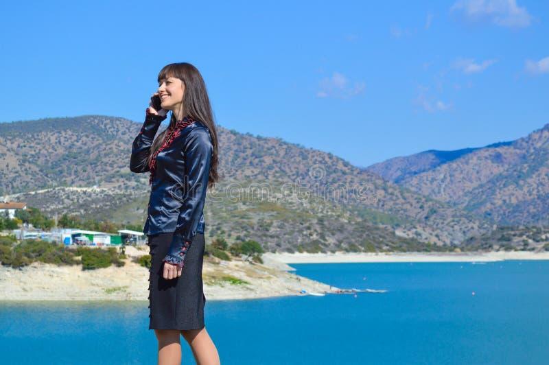 Красивая девушка говорит на мобильном телефоне стоковая фотография