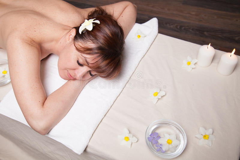Красивая девушка лежа в сауне массажа курорта стоковое изображение