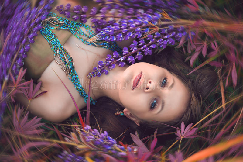 Красивая девушка лежит в цветках lupine стоковое изображение