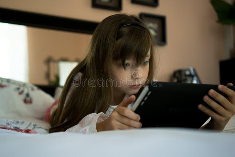 Красивая девушка лежит на кровати и компютерная игра играть стоковое изображение rf