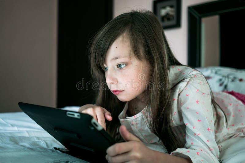 Красивая девушка лежит на кровати и компютерная игра играть стоковая фотография rf