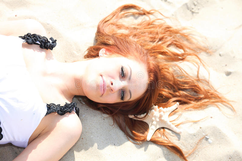 Красивая девушка лежит на морском побережье с каникулами природы раковин стоковое фото