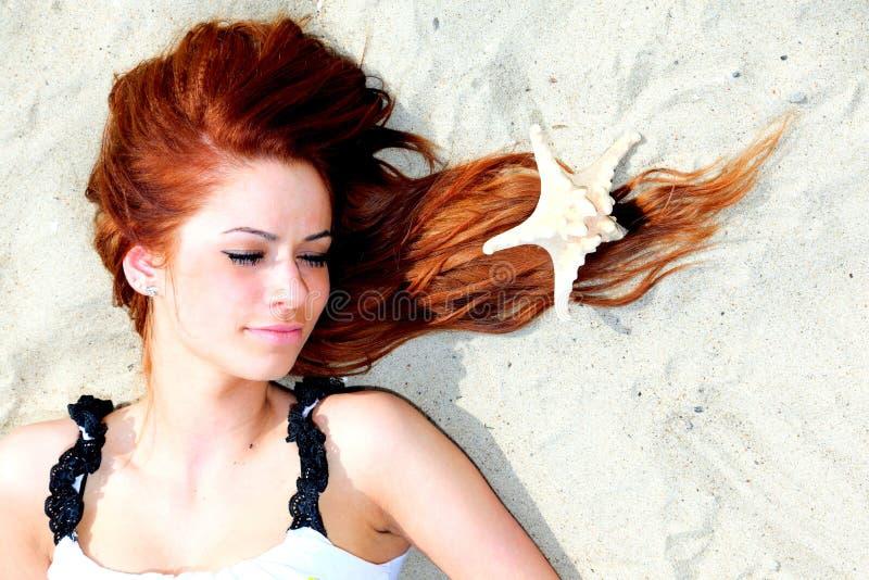Красивая девушка лежит на морском побережье с каникулой природы раковин стоковое фото
