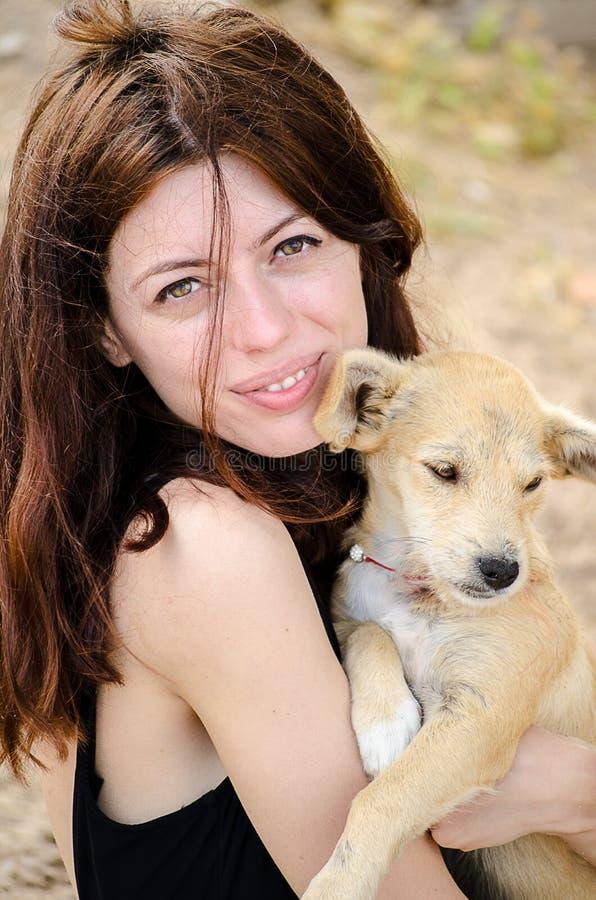 Красивая девушка держа малую бездомную собаку в ее ar стоковые фото