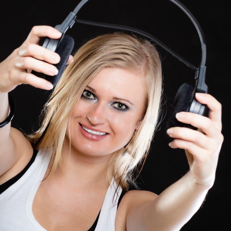 Красивая девушка держа наушники на черноте стоковое изображение rf