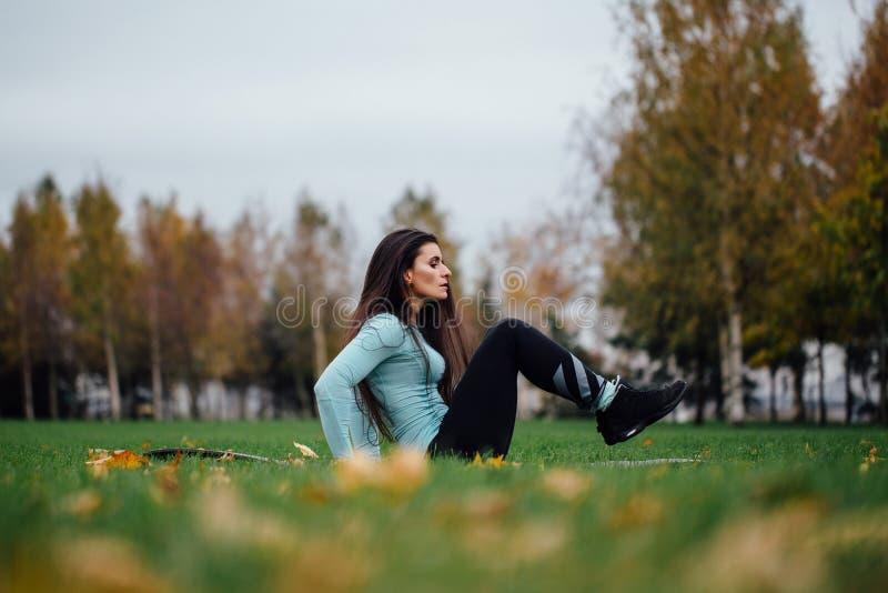 Красивая девушка делает тренировки с прессой на траве стоковое фото