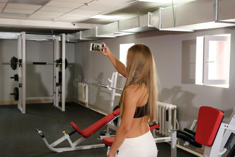 Красивая девушка делая selfie на smartphone в спортзале стоковая фотография
