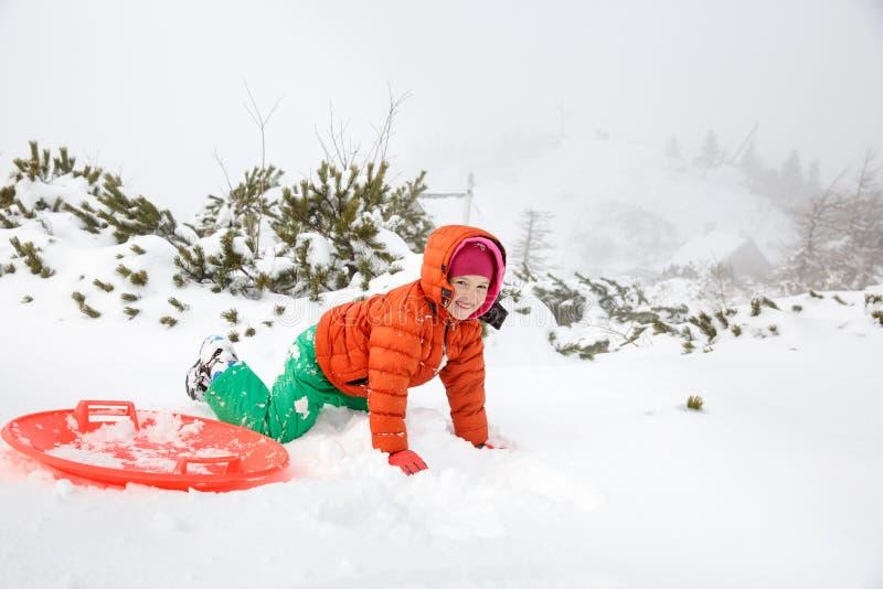 Красивая девушка играя при пластичный скелетон поддонника, падая в снег стоковые изображения rf
