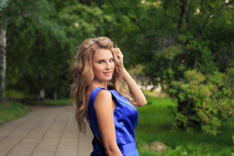 Красивая девушка идет в голубое платье стоковые изображения