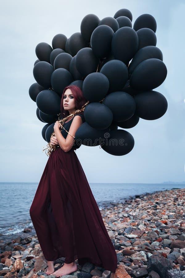Красивая девушка идя с черными воздушными шарами стоковые изображения