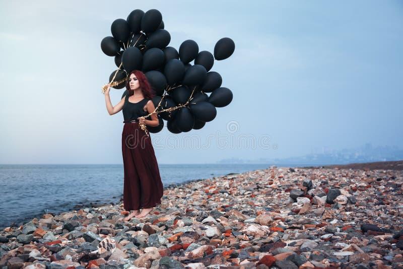 Красивая девушка идя с черными воздушными шарами стоковые фотографии rf