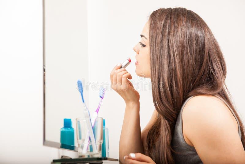 Красивая девушка кладя некоторую губную помаду дальше стоковая фотография rf