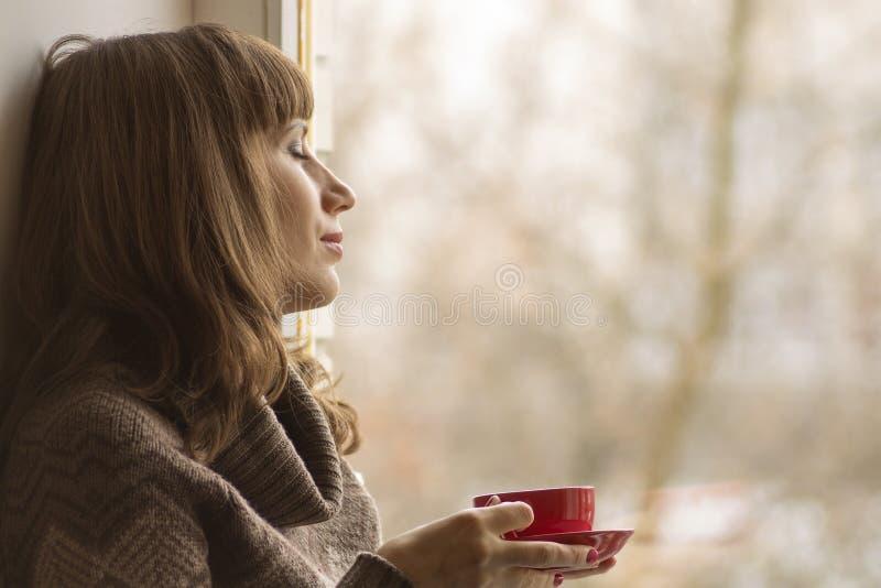 Красивая девушка мечтая с чашкой кофе около окна стоковое изображение rf