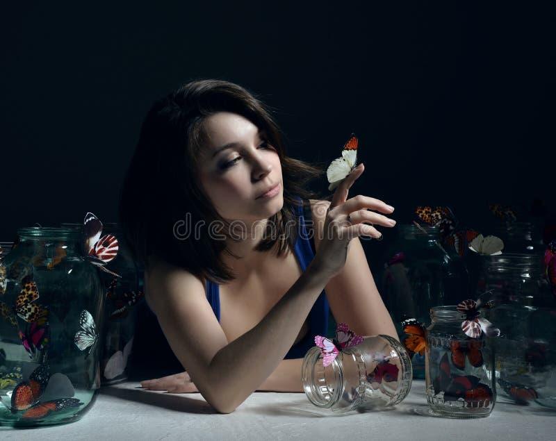 Красивая девушка моды с бабочками в ясных стеклянных чонсервных банках стоковые изображения