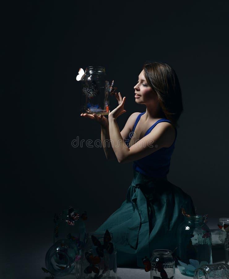 Красивая девушка моды с бабочками в ясных стеклянных чонсервных банках стоковые фотографии rf
