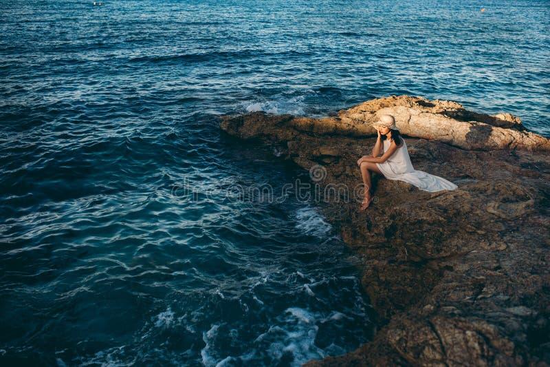 Красивая девушка ослабляет на утесе на океане побережья стоковое фото