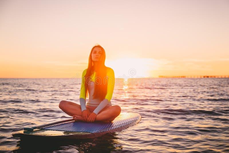 Красивая девушка ослабляя дальше стоит вверх доска затвора, на тихом море с теплыми цветами захода солнца стоковое изображение