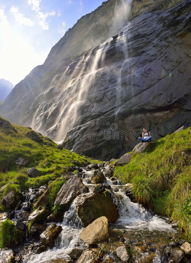 Красивая девушка отдыхая около водопада Lauterbrunnen стоковое фото rf