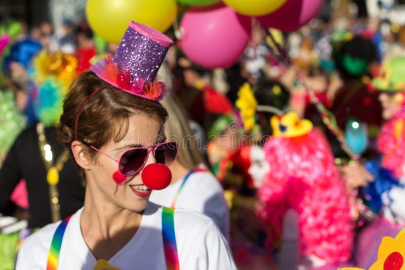 Красивая девушка при красный нос одетый как клоун на масленице стоковые фото