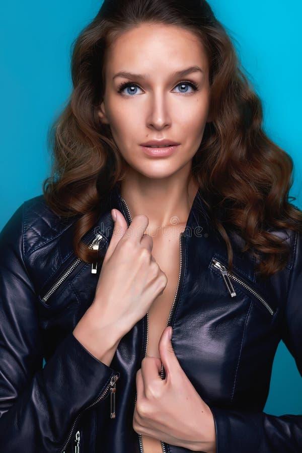 Красивая девушка при темное вьющиеся волосы и голубые глазы держа jacke стоковые изображения rf