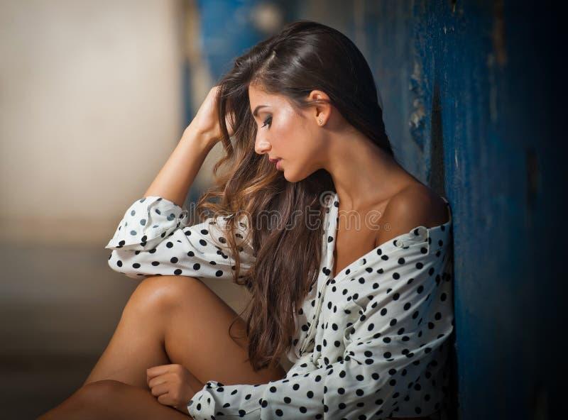 Красивая девушка при unbuttoned рубашка представляя, старая стена с слезать голубую краску на предпосылке Милое брюнет сидя на по стоковое изображение rf