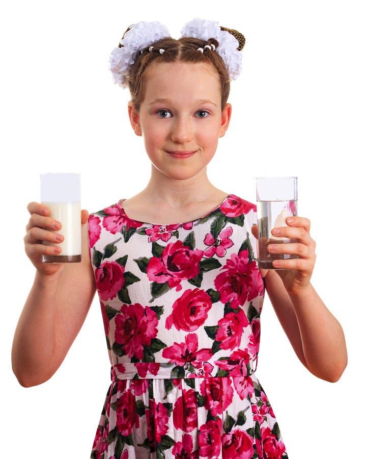 Красивая девушка ребенк держа стекла молока и чистой воды стоковые изображения rf