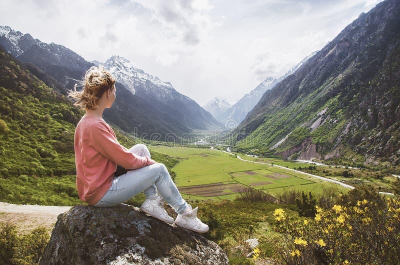 Красивая девушка сидит на утесе в горах и смотрит красивый ландшафт долины горы стоковая фотография rf