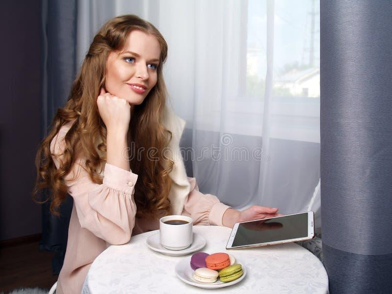 Красивая девушка сидя в кафе стоковые фото