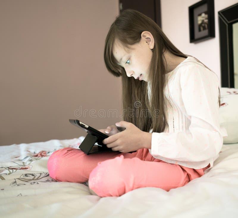Красивая девушка сидя на кровати и играя компютерную игру стоковые изображения