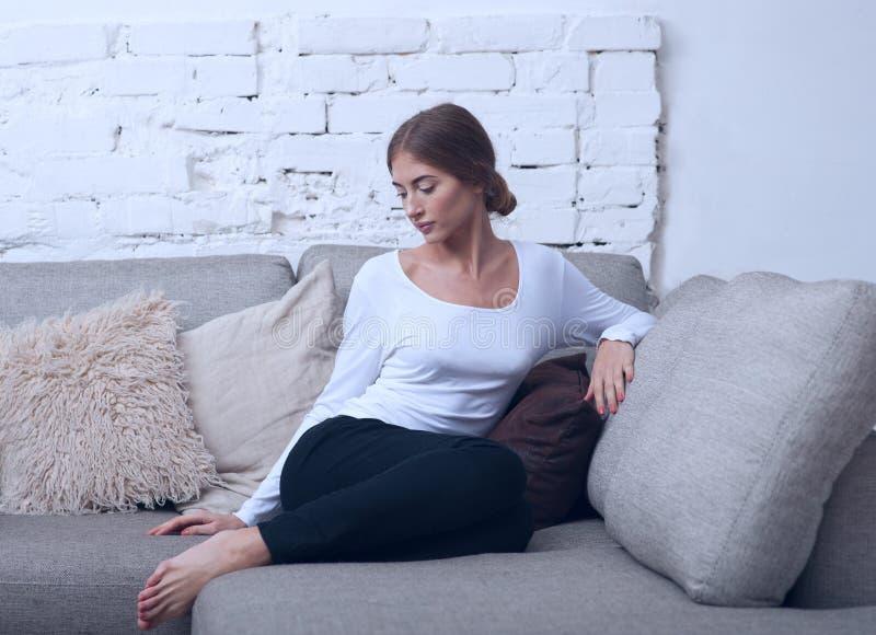 Красивая девушка сидя на софе в голубых тонах стоковая фотография