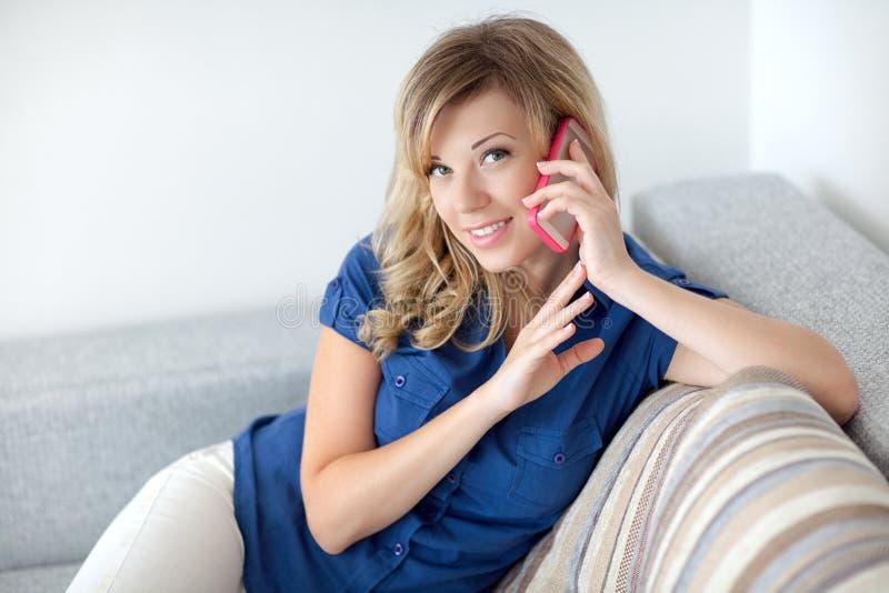 Красивая девушка сидя на софе и говоря на телефоне стоковые фото