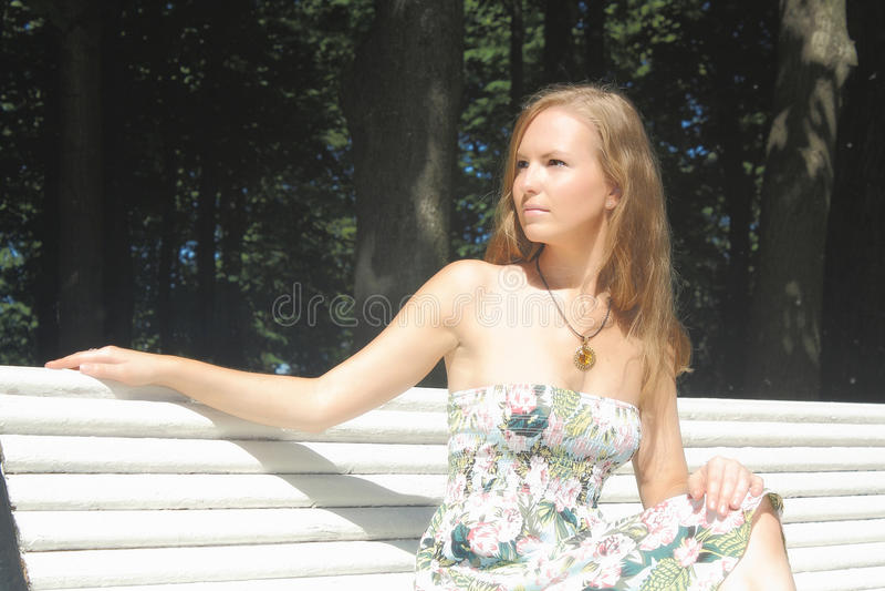 Красивая девушка сидя на стенде стоковое фото rf