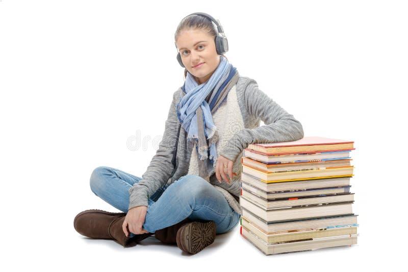 Красивая девушка сидя положив ногу на ногу, слушая музыка на белизне стоковое изображение rf