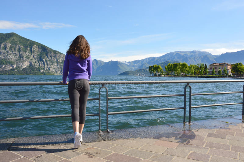Красивая девушка смотря ландшафт озера и гор солнечный на предпосылке внешней Концепция образа жизни перемещения здоровая стоковая фотография rf