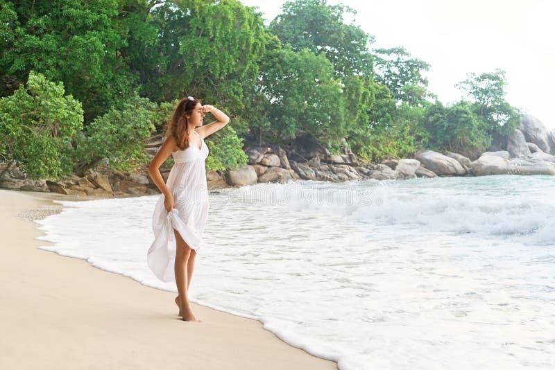Красивая девушка смотря далекий находиться на береге моря в Таиланде стоковые изображения