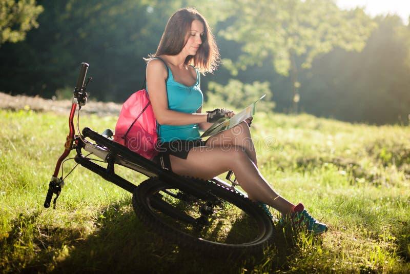 Красивая девушка спорта с велосипедом прочитала карту стоковое фото
