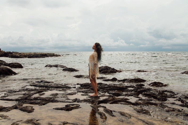 Красивая девушка стоит в воде на пляже, красивых пуках вокруг стоковое фото