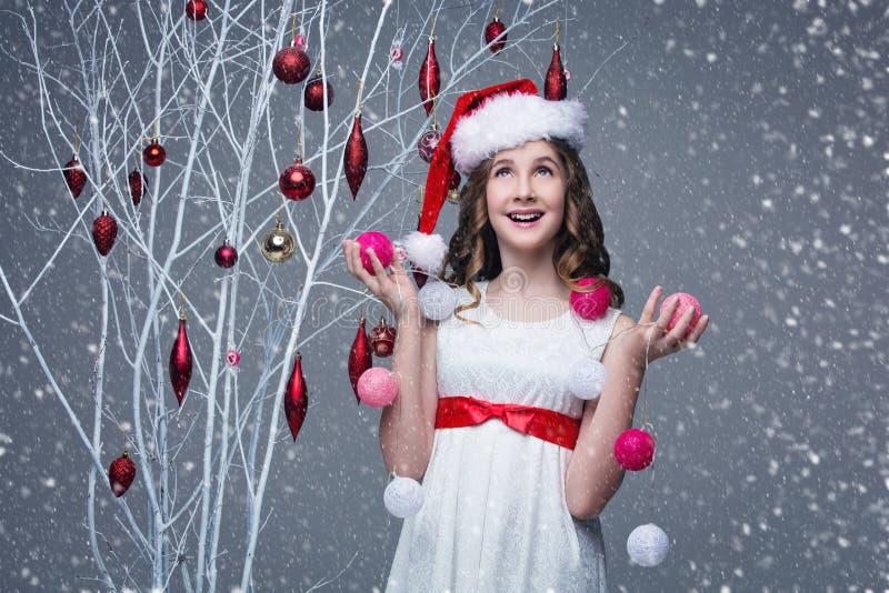 Красивая девушка стоя близко дерево с украшениями рождества стоковая фотография rf
