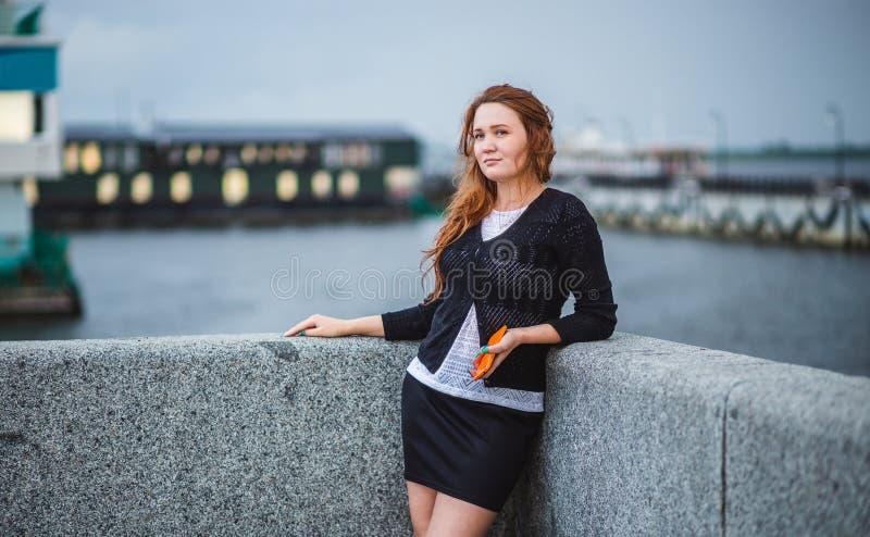Красивая девушка стоя на банке реки Она держа телефон и смотря afar стоковое изображение rf