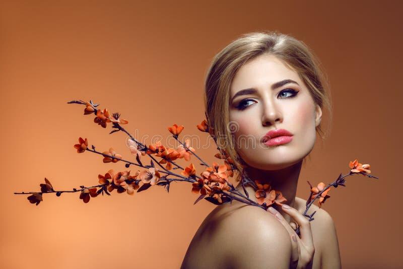 Красивая девушка с ветвью Сакуры стоковая фотография