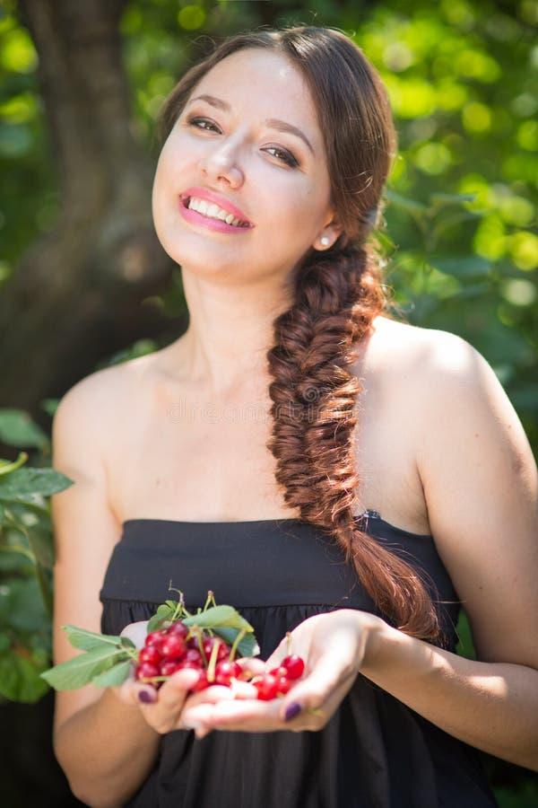 Красивая девушка с вишнями стоковые изображения