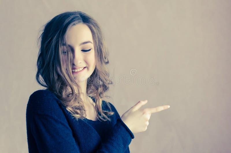 Красивая девушка с вьющиеся волосы указывая к стороне стоковое изображение rf